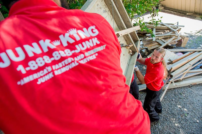 junk king workmen in red company shirts removing old home debris