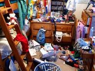guest room that's overflowing with clothes and junk