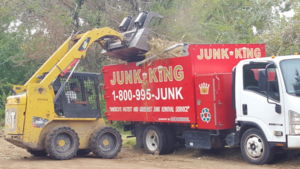 bobcat loading tree and yard trimmings onto a junk king truck