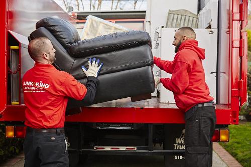 Junk King Servicemen loading sofa onto a junk king truck