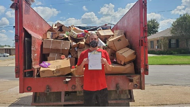 Junk King Ruck filled with old boxes and serviceman standing in the front of the truck
