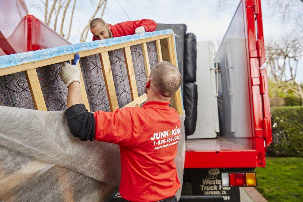 junk king workmen loading household items to truck