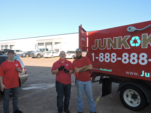 2 Junk King Team members and truck parked outside commercial building