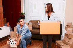 Man and woman packing boxes in apartment
