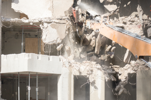 A partially demolished building and excavation equipment
