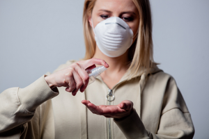 woman wearing grey hoodie and white face mask spraying hand sanitizer