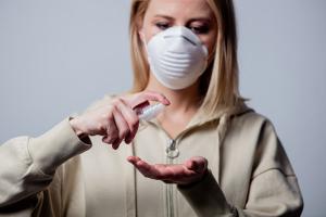 woman wearing grey hoodie and white face mask spraying hand sanitizer
