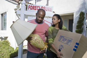 Male with lamp in hand and female holding a box. Red foreclosure sign in background
