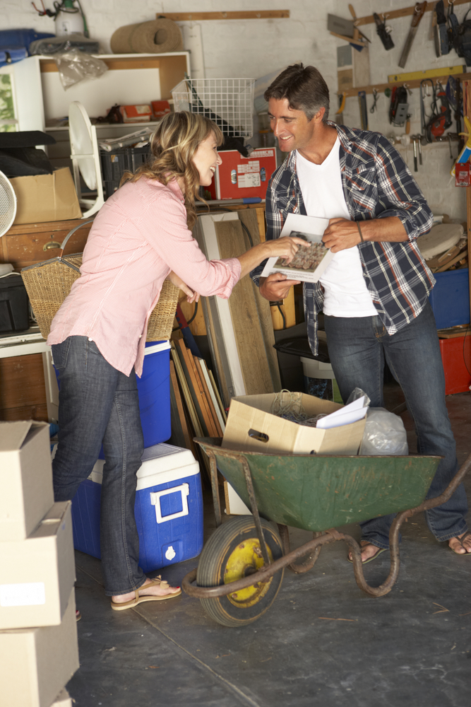 1 caucasian male and female smiling in a garage filled with bulk items