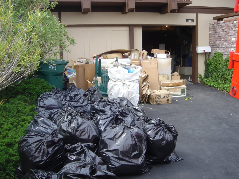 piles of garbage in black bags and old wooden debris in background