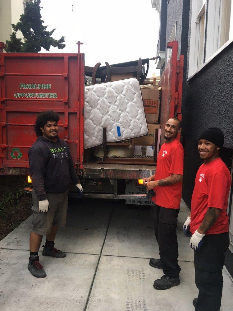 3 Junk King San Francisco workmen loading furniture to the back of a Junk King Truck