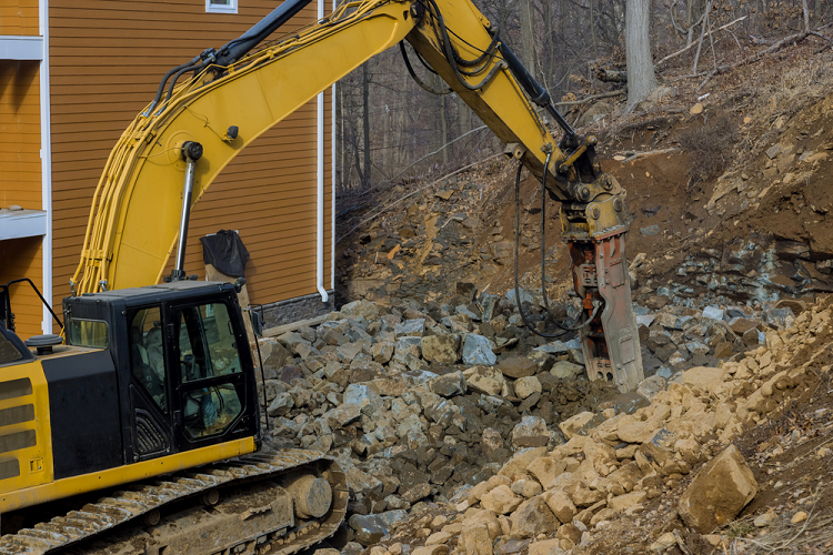 C&D - Yellow Jack hammer unearthing ground and Creating Construction Debris