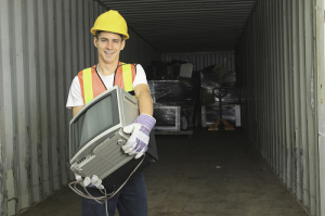 Worker holding television at a TV recycling center