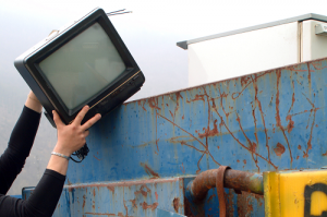 Hands placing TV in dumpster