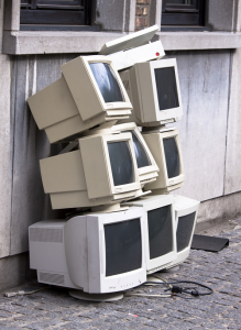 seven white computer monitors piled up outdoors