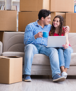 couple sitting on sofa with boxes stacked behind