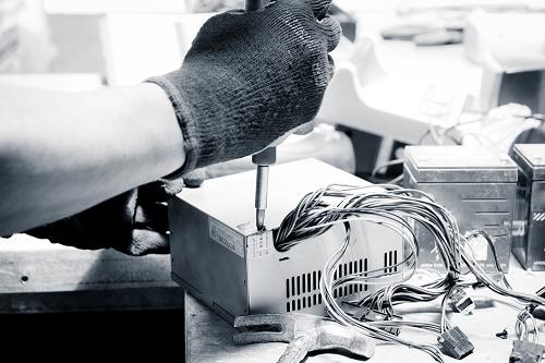 e-waste facility technician dismantling parts in e-waste plant