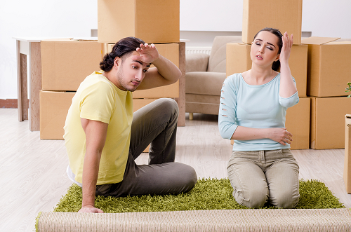 male and female sitting on rug with boxes in the background