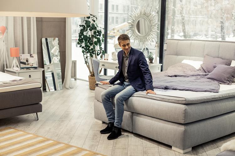 man sitting on brand new mattress in store