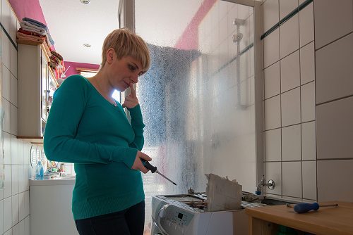 woman holding a screwdriver standing in front an old and broken washing machine
